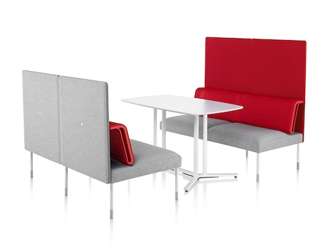 A pair of two-person Public Office Landscape seats in red and grey face each other with a rectangular table between.