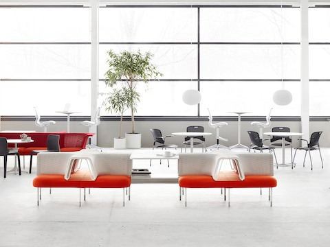 A collaboration area featuring social chairs from the Public Office Landscape system in shades of orange, red, and white.