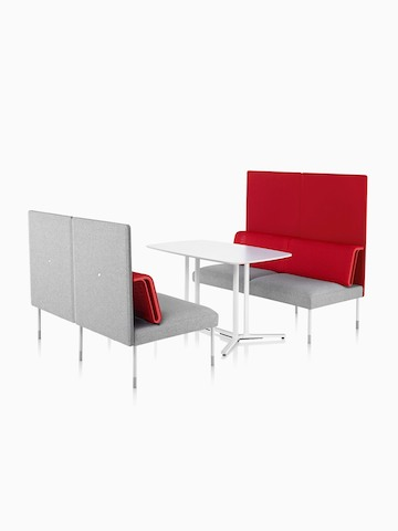Two-seat sectionals face each other across a table to form a small meeting or social space.