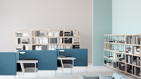 An open work area with a blue sofa, two shelving units, and Public Office Landscape solo workstations in a zigzag configuration.
