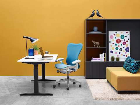 A workspace featuring a Ratio height-adjustable desk, blue Mirra 2 office chair, and bookcase.