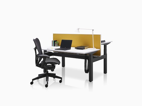 Back-to-back Ratio height-adjustable desks positioned at different heights and separated by a yellow privacy screen.