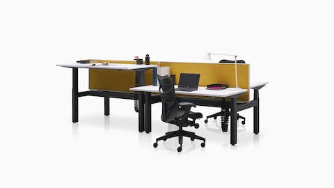Adjacent Ratio adjustable desks positioned at standing and seated heights with yellow privacy screens.