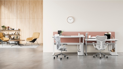 Adjacent Ratio height-adjustable desks positioned at standing and seated heights with yellow privacy screens.