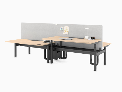 Two Ratio sit-to-stand desks positioned back-to-back with a yellow privacy screen between.