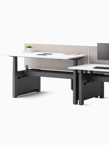 Two Ratio sit-to-stand desks positioned back-to-back with a yellow privacy screen between. Select to go to the Ratio product page.