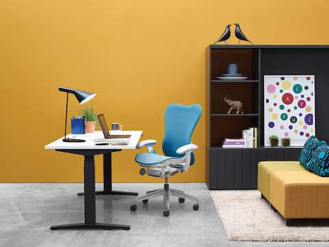 A Ratio height-adjustable desk paired with a blue Mirra 2 office chair in a casual work setting.