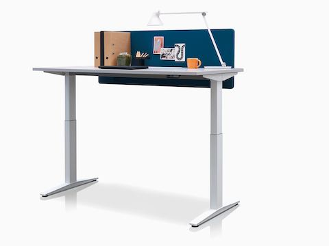 A rectangular Ratio height-adjustable desk with an attached privacy screen, positioned at standing height.