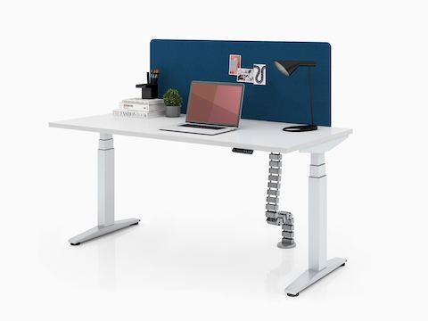 A rectangular Ratio height-adjustable desk with an attached privacy screen, positioned at seated height.