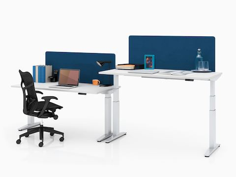 Adjacent workstations featuring Ratio height-adjustable desks, one at seated height and one at standing height.