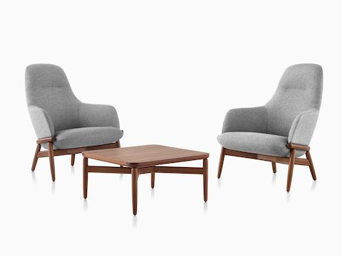 Two gray upholstered Reframe High-Back Lounge Chairs on either side of a walnut Reframe Table.