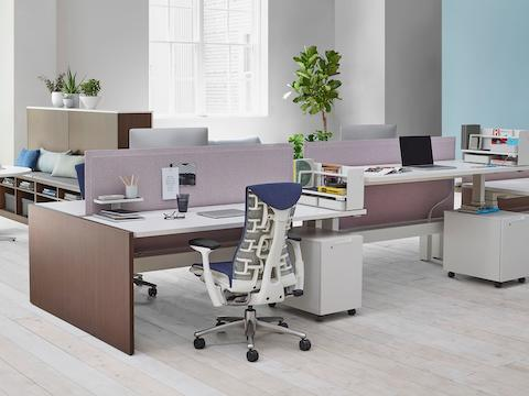 An office setting with a Renew Link standing desk system with blue Embody office chairs, dark wood supports, and purple fabric divider panel.