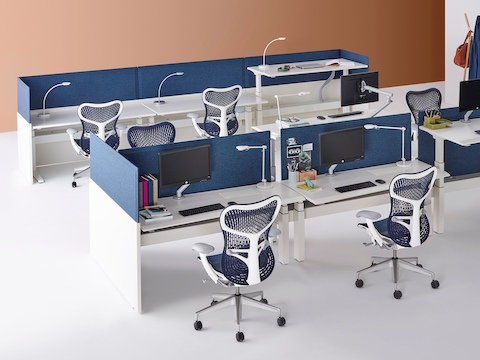 Two groupings of Renew Link standing desk systems with blue Mirra 2 office chairs, white work surfaces, and blue fabric divider panels. Two of the nine desks are raised to standing height.