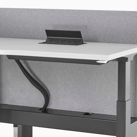 A close-up view of a Renew Link standing desk system with work surface power access and under-surface cable management.