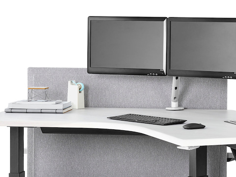 A close-up view of a Renew Link standing desk system with 120-degree work surfaces, black legs, and light gray divider panel. Select to go to the Renew Link standing desk system's specs page.