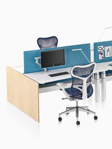 A close-up view of a Renew Link standing desk system with blue Mirra 2 office chairs and blue fabric divider panels.