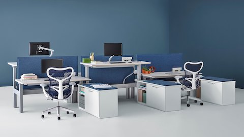 Blue Mirra 2 ergonomic office chairs at Renew Link height-adjustable workstations with blue fabric dividing screens and ergonomic monitor arms.