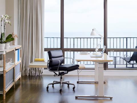 A home office with a water view, a rectangular Renew Sit-to-Stand Table, and a black Eames Soft Pad Chair.