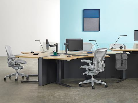 An open workplace with an oval Renew Sit-to-Stand Table positioned at standing height and four black Aeron office chairs.