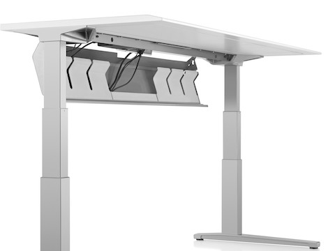 The underside of a Renew Sit-to-Stand Table, showing the cord trough in open position.