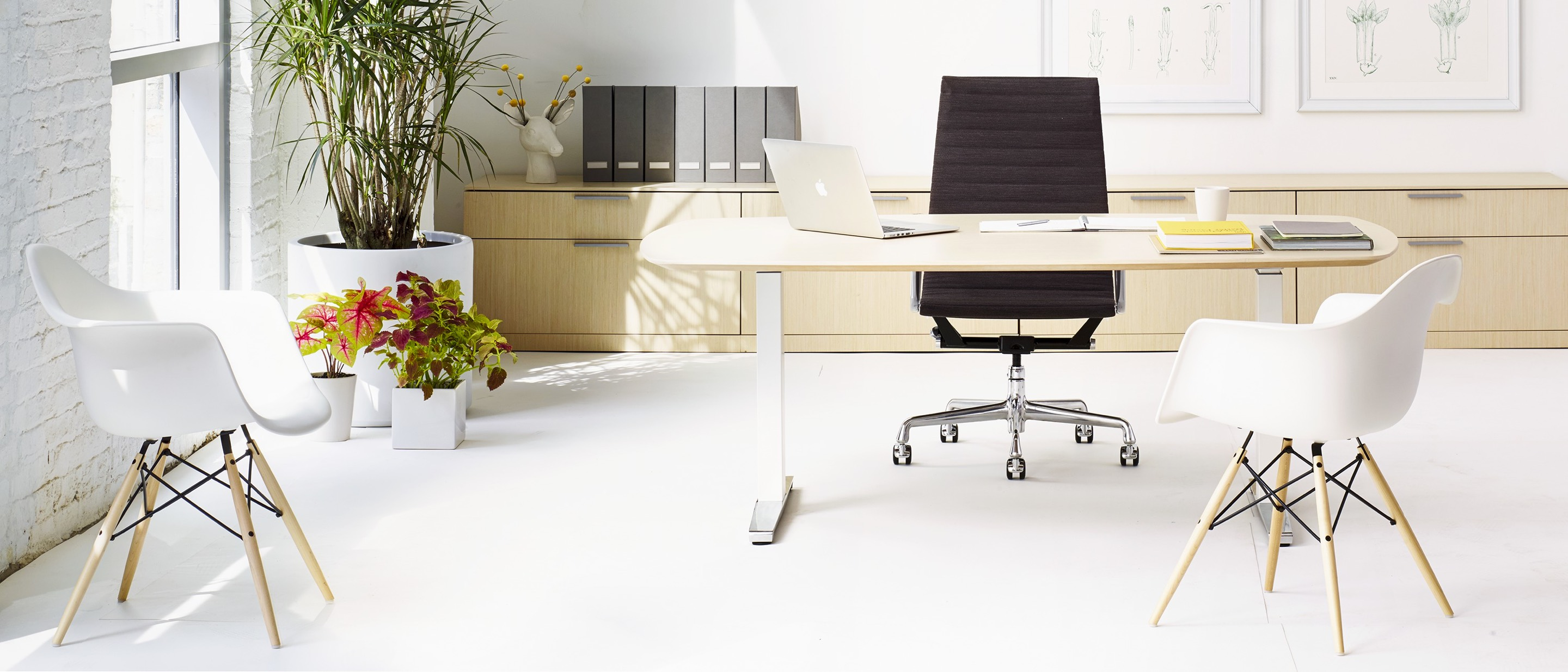An office featuring an oval Renew Sit-to-Stand Table at a seated height, black Eames Aluminum Group Chair, and two Eames Molded Plastic Armchairs.