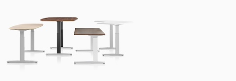 Four Renew Sit-to-Stand Tables in various shapes and top finishes, positioned at various heights.