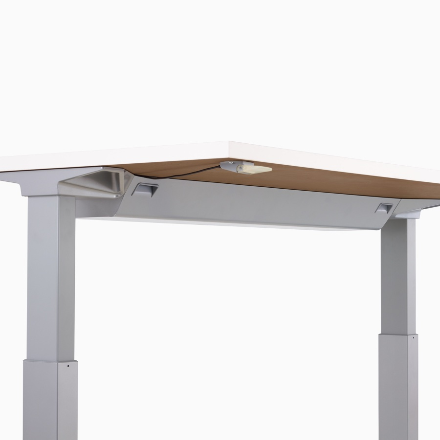 Viewed at an angle, the underside of a Renew sit-to-stand desk with a high-density cable tray and intuitive paddle.
