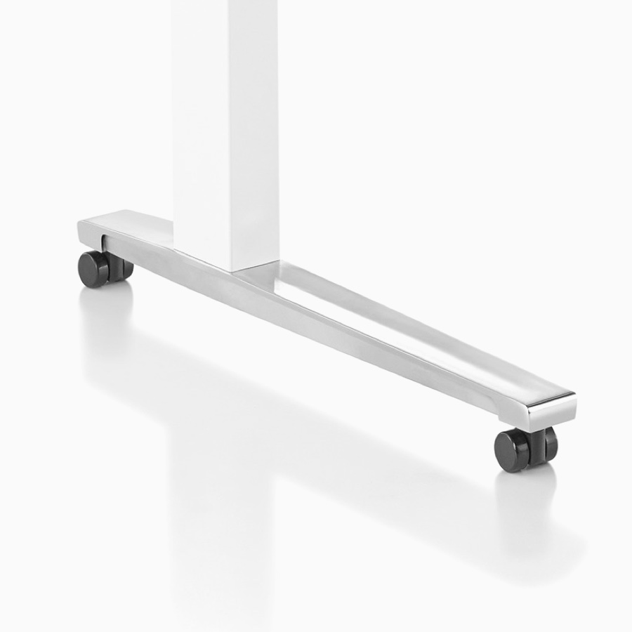 Close-up of Renew Sit-to-Stand Table's white C-leg base, polished aluminum feet with casters.