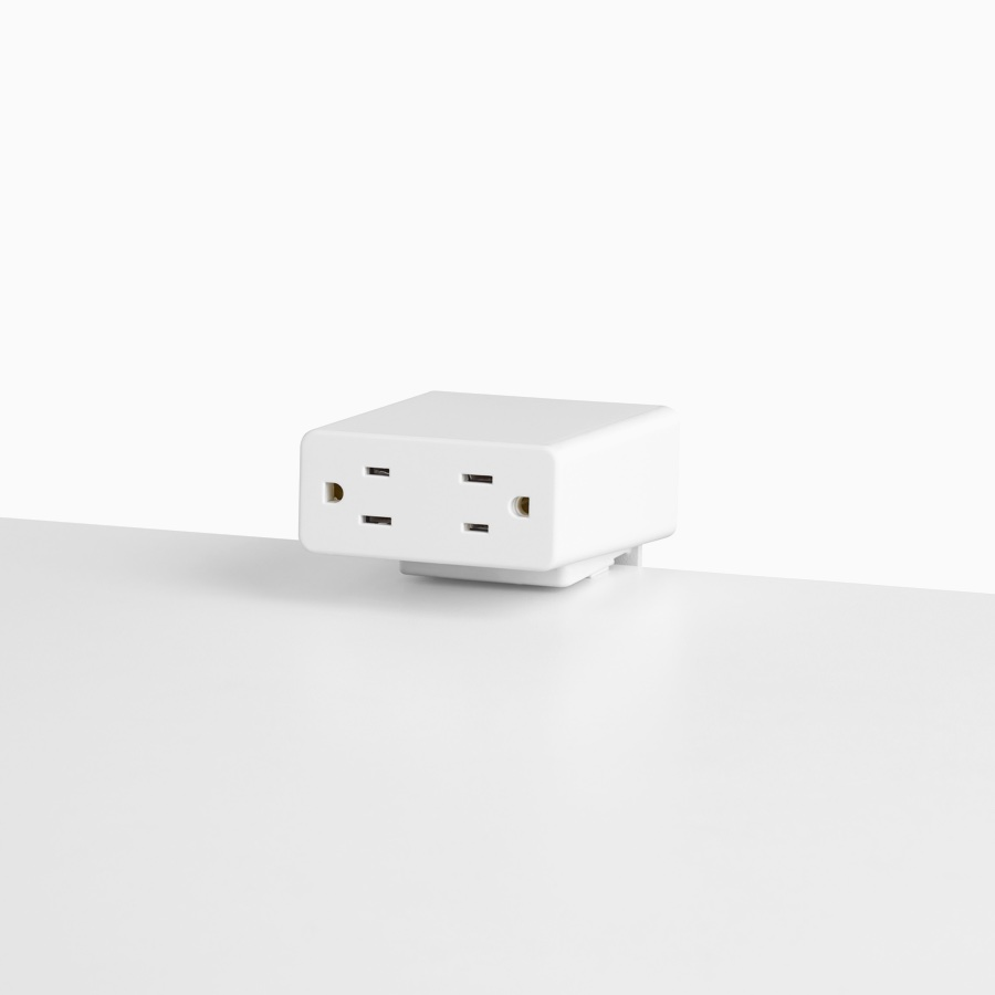 Viewed at an angle, a white Logic Mini with two power outlets, attached to a white work surface.