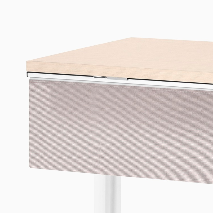 Viewed at an angle, a rectangular Everywhere Table with clear on ash woodgrain laminate work surface, white base, and a fabric modesty panel.