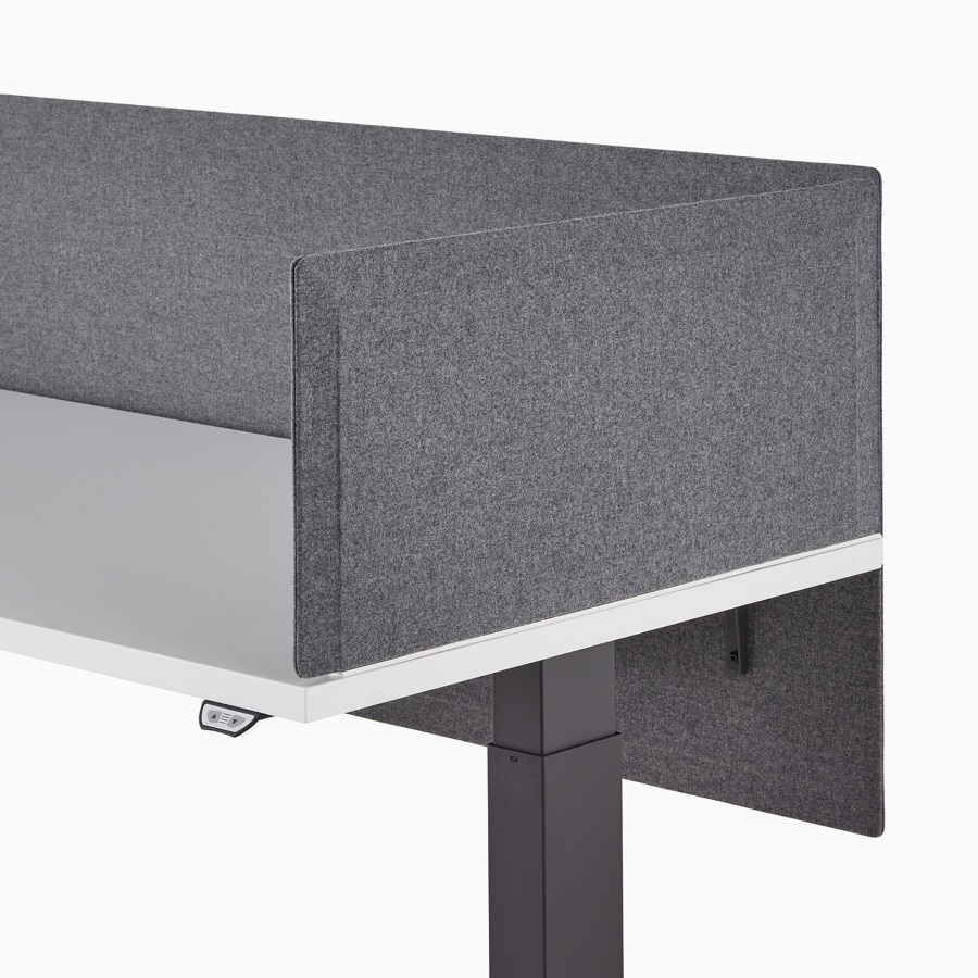 Close-up of a dark gray, tapered edge, fabric delineation side screen and surface-attached privacy screen on a Motia Sit-To-Stand Table.