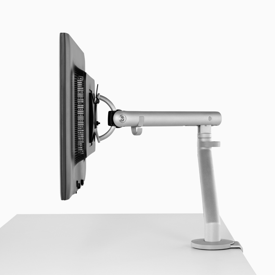 Side profile of a silver, single Flo Monitor Arm holding a screen and attached to a white work surface.