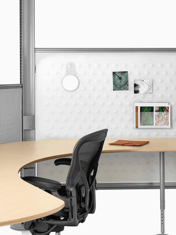 Black Aeron ergonomic office chair at a Resolve wraparound desk with fabric dividing panels.
