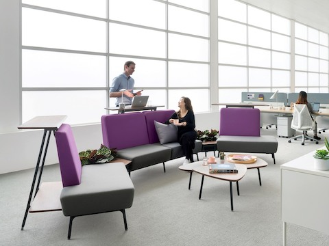 Two colleagues converse in an interaction space featuring purple-and-grey Sabha seating elements backed by standing surfaces.