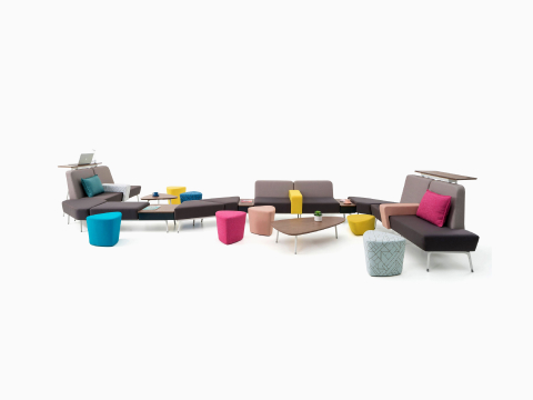 A curvy configuration of Sabha Collaborative Seating elements, along with colourful ottomans, coffee tables, and Ode Lamps.