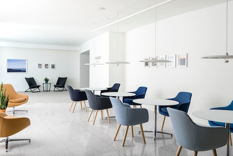 A casual gathering space featuring orange Saiba Lounge Chairs, black Scissor Chairs, and Saiba Side Chairs in shades of blue.