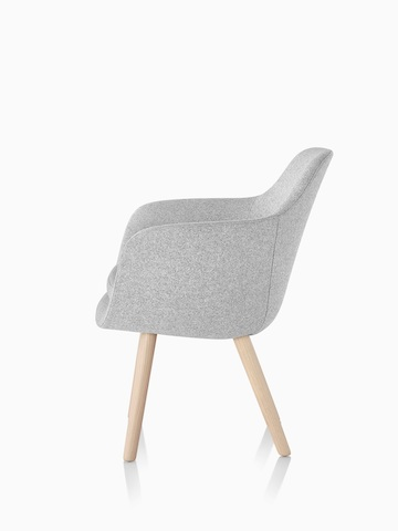 Profile view of a light gray Saiba Side Chair with an upholstered bucket seat and wood legs.
