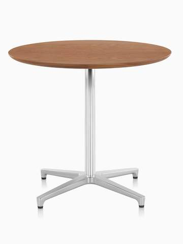 A round Saiba Table with a medium wood finish. Select to go to the Saiba Tables product page.