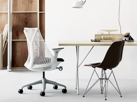 Small office with a white Sayl office chair, black Eames Molded Fiberglass Chair with wire base, and Nelson X-Leg Table.