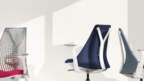 Three Sayl office chairs, one white with suspension back, one blue with upholstered back, and one light gray with upholstered back.