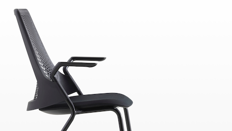 Profile view of a black Sayl Side Chair with a suspension back and upholstered seat.