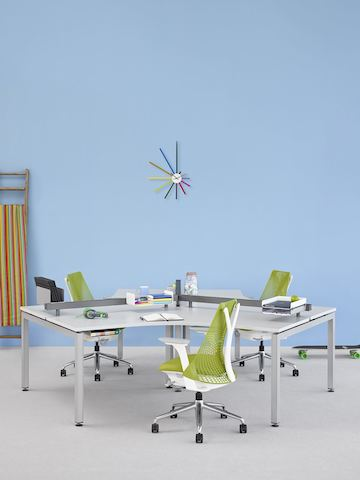 A cluster of three 120-degree Sense Desks with white surfaces, each with a green Sayl office chair.