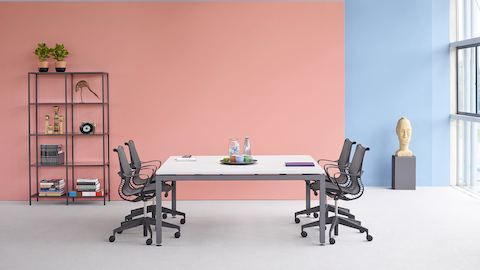 A bright meeting space featuring four black Setu office chairs around a square Sense table.