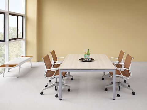 Natural light fills a meeting room featuring a Sense table with a light woodgrain top and copper-coloured Setu office chairs.