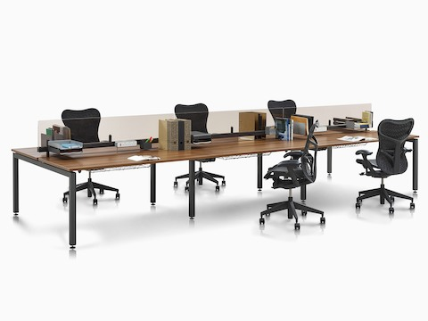 Back-to-back Sense bench desks divided by glass seated-height screens and paired with black Mirra 2 office chairs.