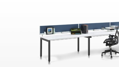 Sense bench desks with white surfaces and blue seated-height screens.