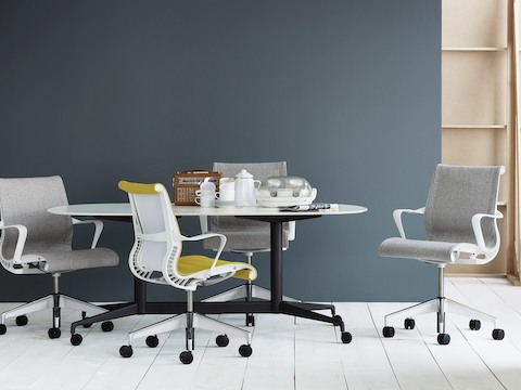 Light gray and yellow Setu office chairs around a Locale table with a white top and black base.