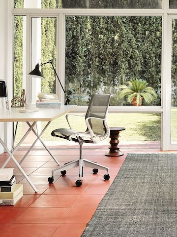 Black Setu office chair and a Nelson X-Leg Table in a glass-walled home office overlooking the outdoors.