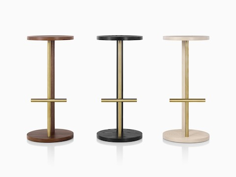 Family of Spot Stools in white ash, walnut, and ebony with brass finish, viewed from the front.