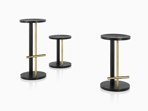 Family of Spot Stools in ebony with brass finish, viewed at an angle.
